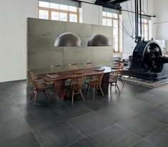 Monza Black porcelain tiles in a large, industrial-themed dining hall