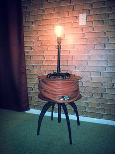 I attached an old fire hose reel to a low stool to make a bedside table