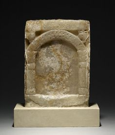 "sculpture; Ancient South Arabian; Yemen; Yemen. Calcite sculpture fragment representing front of a temple or semi-circular aedicula supported by corinthian capitals; incomplete South Arabian inscription in Qatabanian, stating ""Image of Rabi'at ...""."
