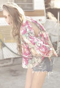 Oversized watercolor floral print button front collared blouse  featuring a wide, cropped fit, slit detail at shoulder, and an  asymmetrical hem that is longer in the back.