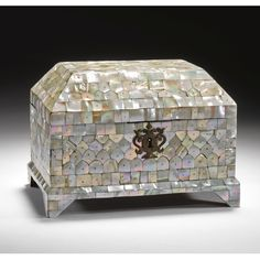 A MOTHER-OF-PEARL CASKET, INDIA, GUJARAT, 17TH CENTURY the wood body of rectangular form supported on four raised feet with vaulted cover with two palmette hinges and foliate lock-plate, the exterior decorated with plaques of mother- of-pearl secured with brass pins, the top and sides with imbricated panels enclosed by rectangular and polygon borders, painted red interior and base