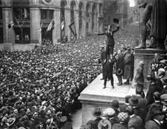 Douglas Fairbanks holding up Charlie Chaplin in front of crowd to promote Liberty Bonds, Lower Manhattan, NYC, 1918.