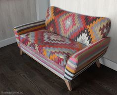 A kilim-upholstered loveseat. The modern lines provide a contrast with the traditional textiles – and also highlight the bold graphics of the design. Evelyn Loveseat from Kim Salmela. Design by This Way Home