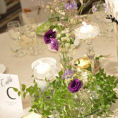 「テーブル装花とテーブルナンバー 投げ入れのお花、グラスキャンドル、ミラー そしてキャンドル作家の友達のキャンドルー キャンドルの下の方をグリーン&パープルのグラデーションにしてもらいました キャンドルがガッツリうつってるpicがなくて残念ですが ムービーがきたらぜひ載せたい素敵なキャンドルです…」
