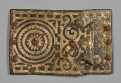 Buckle, 2nd century b.c.; European Iron Age Celto-Iberian; Spain Leaded bronze, silver, iron  This bronze and silver buckle is unusual in that both its top and bottom plaque are preserved, along with remains of the iron rivets used to attach it to a leather belt. Small figurines show warriors wearing similar clasps, suggesting this was designed for use by a soldier. It is typical of a type of buckle produced in the central plain region of the Iberian Peninsula