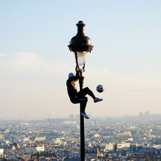Street Soccer Performer at the Sacre Coeur, Paris, France >>> People amaze me! I can't believe this guy is climbing a light post and playing soccer at the same time!