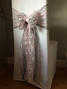 White chair covers with grey / silver organza sash and pink lace sash. Available to hire for weddings and events in Swansea, Cardiff, Neath, Bridgend, Llanelli, Carmarthen and surrounding areas of South Wales from www.affinityeventdecorators.com