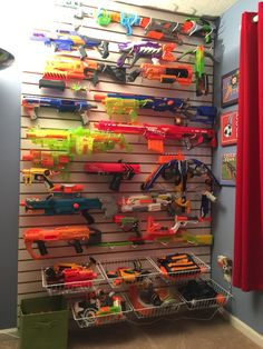 "Nerf gun wall display. This was made from slat wall board purchased at Menards. I also used 6"" white hooks and 15"" white wire baskets purchased on Amazon. This wall is 5' wide by 8' tall."