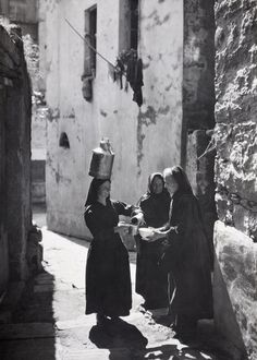 Women sell and buy milk in a narrow alley. Corsica, France. Clifton R. Adams, 1920s