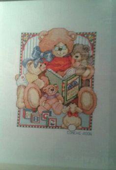 Abuelo oso leyendo un cuento de punto de cruz