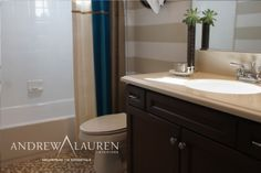 Warm Natural Stone Vanity Countertop And Wallpaper Color Scheme Give This Bathroom The Feel Of A Sandy Beach On Tropical Island