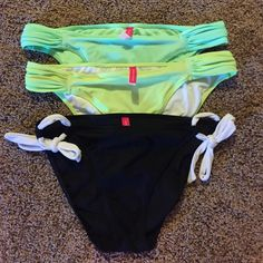 VS Bikini bottom bundle 2 pair of rousched bottoms in seafoam green and a neon yellowish green. Black pair have white adjustable side ties. All have a matte finish material and full coverage on rear and sits low on hips. Victoria's Secret Swim Bikinis