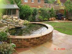 A raised pond like this brick one makes caring for the fish and the water much easier.