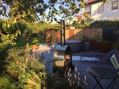 Wohnraum Garten. LIGUNA Holzlager aus Cortenstahl in Kombination mit Lärche Rombus Sichtschutz.. Das CONTURA Pflanzgefäß für die Kräuter runden das Bild ab.