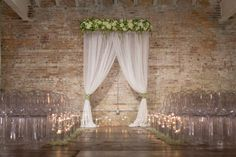 White chiffon accent draping with green and white florals for a dramatic ceremony backdrop. Glass cylinders with floating candles. Florals by Design Perfection, Draping and Custom Cuffs by DP etc, Ghost Chairs from Eventful Furniture & Design. Venue: Bakery 105, Wilmington, NC