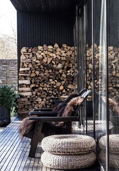 Nordic space on the terrace with a large firewood stack and outdoor wooden chairs with brown lambskin.