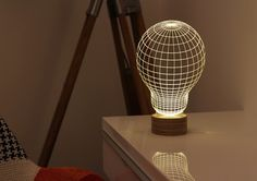 """This simple, minimalist table lamp will make your guests do a double-take. The design etched into the """"bulb"""" creating 3D forms on a 2D piece of acrylic. The soft glow and the stunning wire-sculpture that are etched into the lamp makes the Bulbing an intriguing and beautiful addition to any room in your home."""