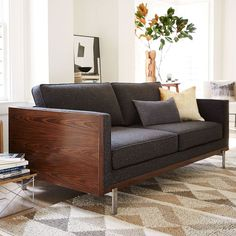 NEW!  Encased in a rosewood-finished wood frame and perched on metal legs, the Wyatt Sofa marries a modern design with cozy comfort. Welted seams along the cushions give it a tailored look.