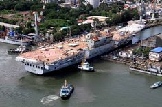 Indian's new aircraft carrier maneuvers to enter its dock in Cochin in India, 10 June 2015.