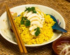 """Gekochtes Hähnchen auf einem Reis, der mit Ingwer gedämpft und mit Kurkuma gefärbt ist.  Hähnchen mit Reis, eine Spezialität der chinesischen Provinz Hainan ist ein in China weit verbreitetes Gericht. Die Hoi An Spezialität zeichnet sich aus durch die Verwendung von Kurkuma, das dem Reis ein schöne gelbe Farbe und einen aromatischen Geschmack gibt. Zusätzlich gibt es die klassische vietnamesische Dipsauce """"Nuoc Mam Pha"""" und die obligatorischen frischen Kräuter."""