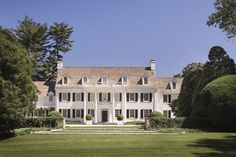 White clapboard traditional in Lattingtown, NY on the North Shore of Long Island by Ferguson & Shamamian. Gorgeous symmetrical facade is flanked by two subtly asymmetrical set-back wings. Perfectly scaled dormers, pediment, portico, and columns. Dropped lantern and round boxwoods are the cherry on the sundae.