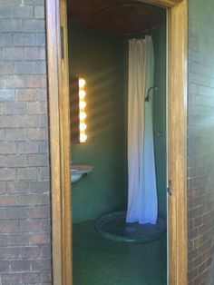 Here is his European-style bathroom that is enclosed in the bricked cylinder that floats in the space. The shower is basically open to the room, with another wooden floor drain nearby and a circular curtain.