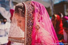 An Indian bride and groom wed in a vibrant hot pink Punjabi ceremony.