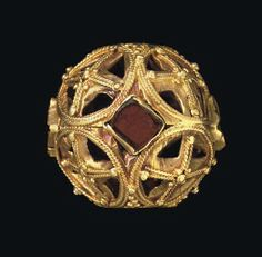 A BYZANTINE GOLD AND GARNET SPHERICAL BEAD CIRCA 8TH-9TH CENTURY A.D.