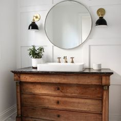 Bathroom with an antique vanity and circular mirror | Park and Oak design
