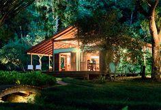 Jardim para três casas com espécies tropicais - Casa. enquanto o mar se enche de reflexis prateados, o jardim ganha focos de iluminação que realçam as nuances e silhuetas das plantas, especialmente as mais altas, como o bambú e a centenária figueira. Projeto luminotécnico de Tania Manela Kurc.