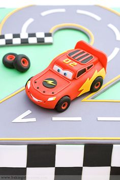 Lightning McQueen Cake from Baking Obsession - I like the street with grey vs black...and probably out of fondant? I have a LM toy for the actual car. Like the grass color base.
