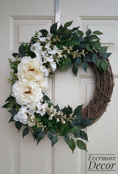 This handmade wreath is on a grapevine base and features off-white peonies as well as an assortment of leafy stems, off-white florals, and small succulents on either side. This wreath is for both outdoor and indoor display and is great for all seasons. The neutral florals make