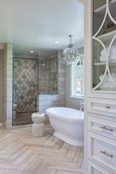 Master bathroom with herringbone tile on floor, freestanding tub and walk in shower | Artistic Tile & Stone by natalie-w