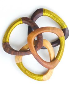 Luscious gold thread winds around hand carved wood to create this striking piece. Stack them high, or pair with another bright bangle. In assorted hues.