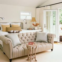 This Chesterfield sofa with striped linen lightens the mood and adds oomph to the room's focal point—the bed! | Coastalliving.com