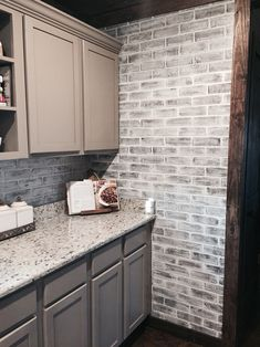 Lowes brick panels painted white. Brick backsplash. Paint color- studio taupe by Behr faux brick