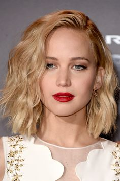 Jennifer Lawrence takes her beachy bob into the winter season with red lips and sleek gold accessories.