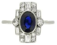 diamondsinthelibrary: Art Deco sapphire and diamond ring, English, circa 1935. A platinum ring set with one central oval old cut sapphire in a millegrain collet setting with an approximate weight of 1.00 carats, flanked by two round old cut diamonds in millegrain bead settings surrounded by a vertical stepped bezel set with eight additional round old cut diamonds in millegrain bead settings, all ten old cut diamonds with an approximate total weight of 0.30 carats, and six rectangular…