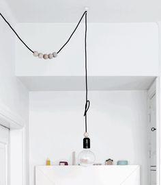 EINE LAMPE, DIE WIE SCHMUCK WIRKT Verwandeln Sie eine einfache Glühbirne in eine schicke Designerleuchte. Suchen Sie im Bastelgeschäft nach grossen Holzperlen. Lassen Sie sich vom Elektriker oder einem Lampenfachmann eine Fassung mit Textilkabel machen. Fädeln Sie die Holzperlen auf das Kabel.