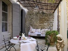 the combination of the stone wall, bamboo rooftop and white cloth curtains