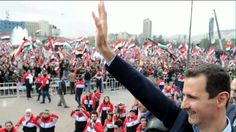 This is a picture of bashar al assad and his people singing the syrian national. The Syrian national anthem is spoken in arabic