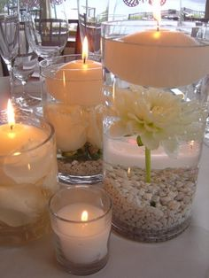 Using the square vases at the hotel, putting either blue or white-ish stones in the bottoms, a fake sunflower in water, and floating candle on top. Just a few for the head table or cake table or somewhere :)