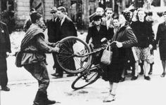 Soviet soldier attempting to steal a woman's bicycle - Berlin, 1945