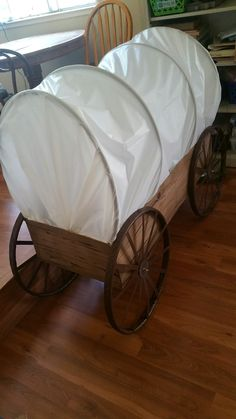 Covered wagon I made for kids camp. Plastic table cloth, cardboard, hula hoops, masking tape, spray paint and of course HOT GLUE!