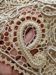 Irish Crochet detail incorporating satiny thread and seed beads into the design