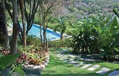 Um caminho de pedras vulcânicas leva à enorme piscina, na parte mais baixa do terreno. Ao redor, há várias espécies tropicais: bananeiras, moreias, palmeiras-garrafa, bromélias e palmeiras-rabo-de-raposa. Projeto do paisagista Gilberto Elkis
