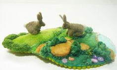 Very small handstitched felt landscape with two miniature rabbits. the scene is a grassy knoll and stream or pond below.