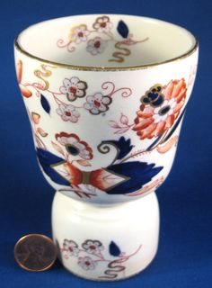 This is an antique double eggcup in the imari style made by T. J. Booth , England 1883-1891 who became Booths in 1891. The egg cup measures 4.5 inches high by 3 in diameter and has hand painted decora