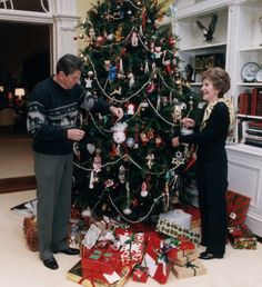 US President Ronald Reagan and First Lady Nancy Reagan decorate the White House Christmas tree with an eclectic set of ornaments on December 24th, 1983.