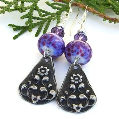 Reminiscent of a field of gorgeous purple flowers, the one of a kind VIOLETA handmade are definite attention grabbers. The captivating earrings feature artisan hand cast pewter charms with a flowing flower and leaf design that have been given a patina for a vintage look.